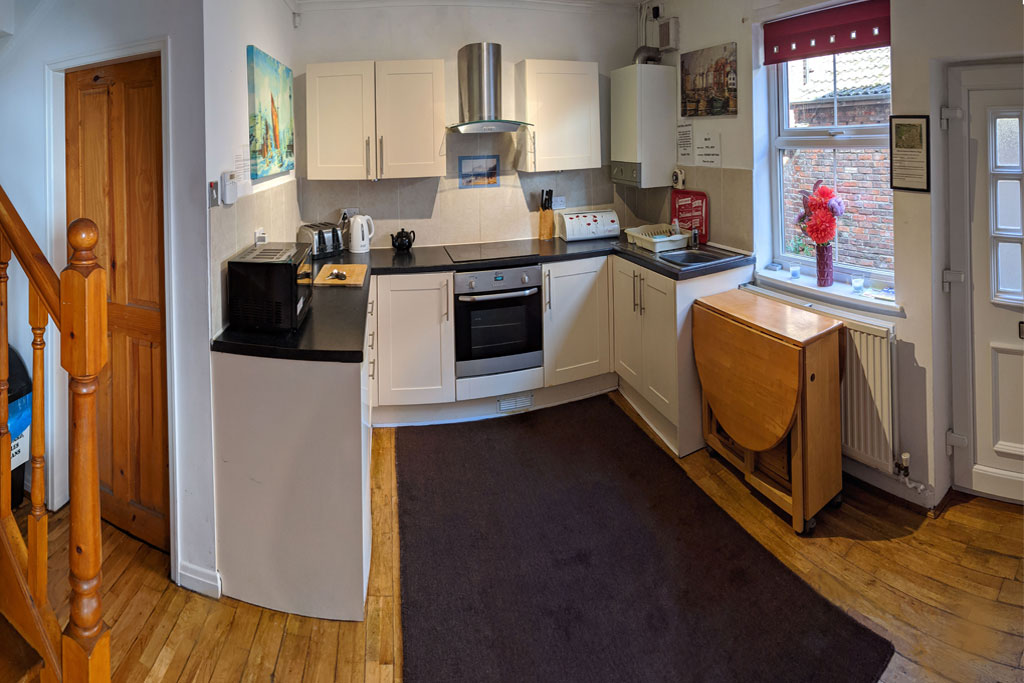 Endeavour Cottage kitchen which separates utility room with dishwasher and washing machine