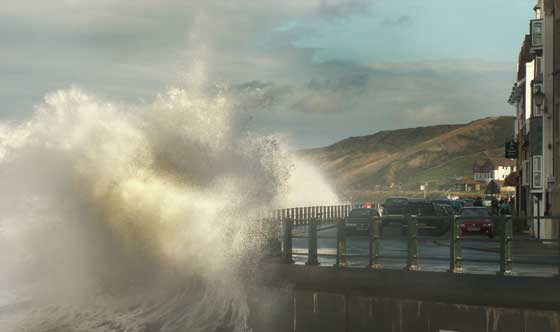 Sandsend with a high tide and crashing waves coming into the harbour wall